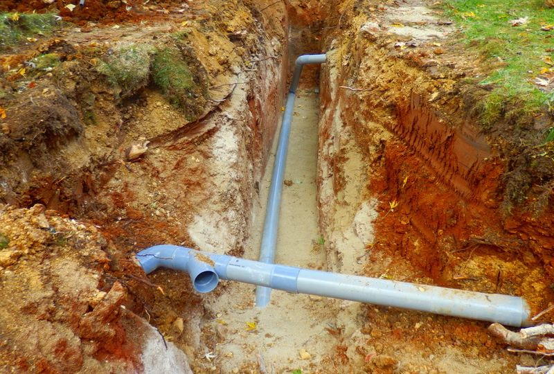 Drainage pipes being installed in a bed of sand for a new water filter system.
