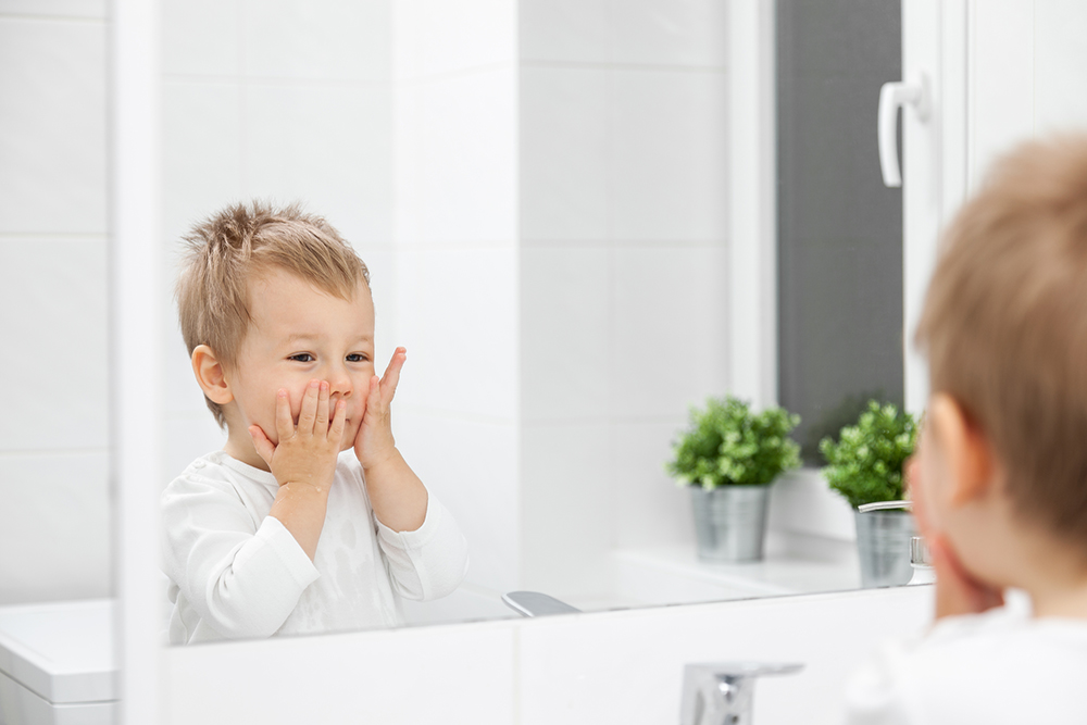 Cute toddler learning how to wash his face