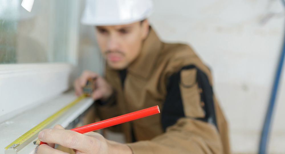 builder measuring a window using a tape measure and pencil