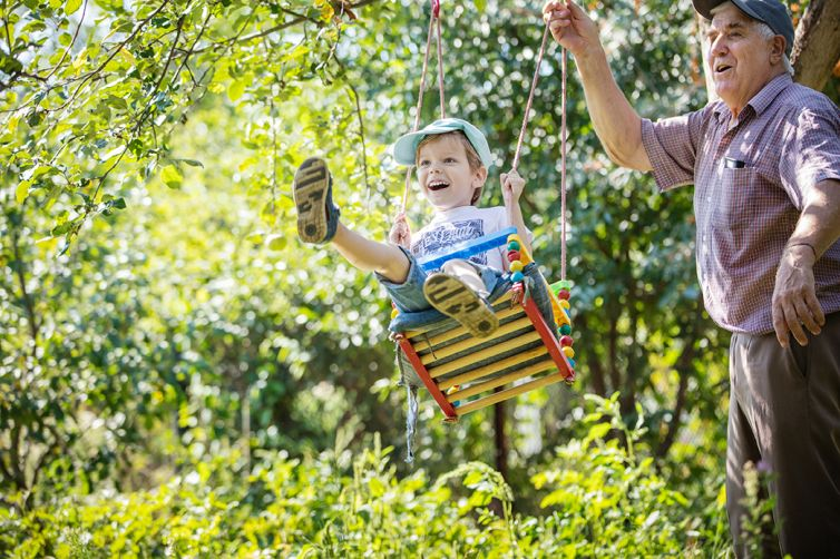 Senior man pushing happy grandson on swing
