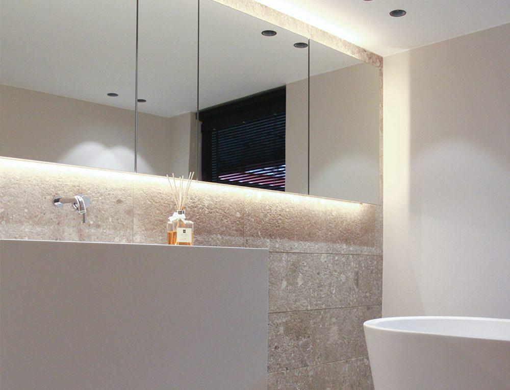 Speglar och belysning skapar rymd i ett litet badrum